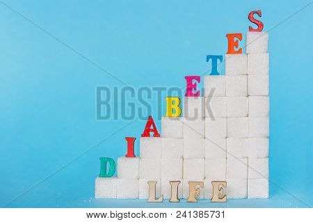 Word Diabetes Of Colored Letters And Life Gray Letters On Ladder Refined Sugar, Blue Background. Сon