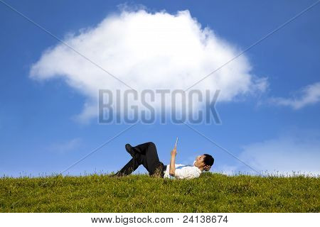 cloud background and happy businessman working with tablet pc on the green grass