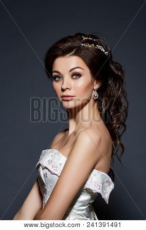 Beautiful Young Woman With Makeup And Fancy Hairstyle. Bride In Wedding Gown. Studio Shot On Grey Ba