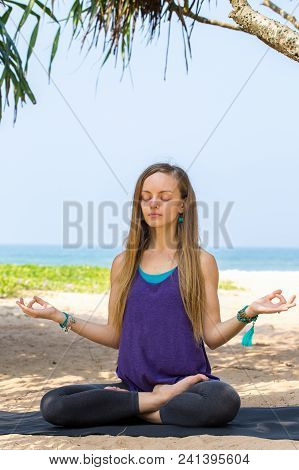 Young Woman Meditating On The Shore Of The Ocean