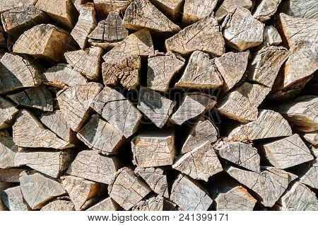 Pile Of Stacked Firewood Prepared For Fireplace And Boiler , Texture Wooden Background. Pile Of Stac