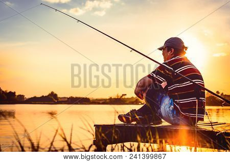 Fisherman Caught Fish. Caucasian Man Catch Fish On Lake. Angler On River Fishing. Fishing Rod Lake F