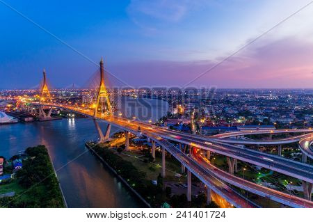 Aerial View Of Bhumibol Suspension Bridge In Bangkok City With Light Trails Of Car On The Road At Su
