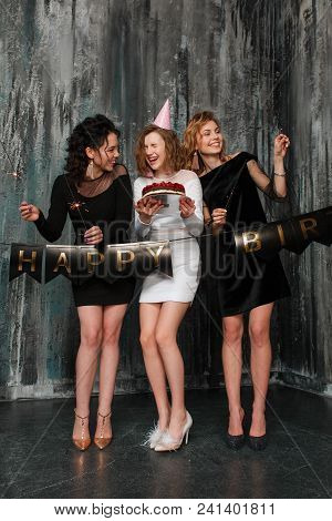 Pretty Girl With Birthday Cake And Her Friends Posing. Full-lenght Portrait On Black Loft Wall Backg