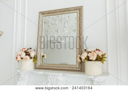 Square Vintage Mirror Frame On The Livingroom Wall Over Fireplace With Photo Frame, And Flowers Bouq