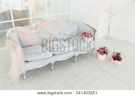 Beautiful Classical White Interior With Vintage Sofa And Mirror Wall. Decorated With Flower Bouquets