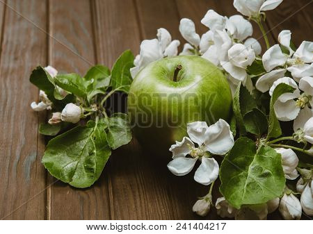 Green Apple With Blossoms On Wooden Table