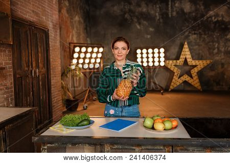 Fitness, Home And Diet Concept. Young Woman With Fruits Standing At Kitchen Table With Retro Bulb Li