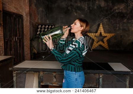 Side View Of Young Woman Drinking Water From Big Glass Bottle In Loft Kitchen Interior.