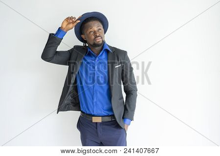 Pensive Dreamy Fashionable Black Man Adjusting Hat And Looking Up. Contemplative African Businessman
