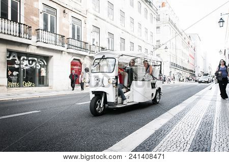 Lisbon, Portugal, May 5, 2018: Tourists Are Traveling By A Traditional Tuk-tuk Vehicle Down A Street