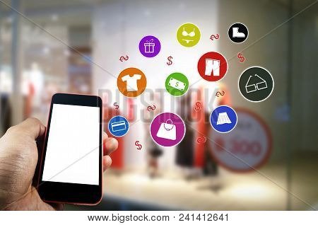 Hand Using Blank Screen Mobile Smart Phone With Showcases Fashion Clothes Display In Department Stor