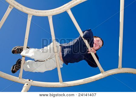 Young boy crawling over monkey bars on playground