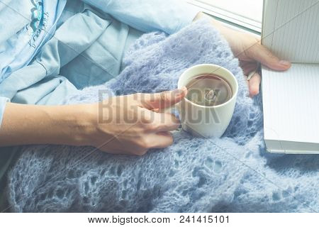 Girl In Warm Woolen Plaid Seating On Window Sill, Drinking Tea And Reading A Book. Winter Weekends I