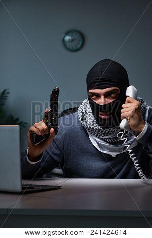Terrorist burglar with gun working at computer