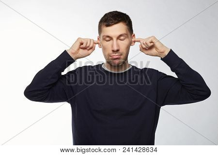 Exhausted Bearded European Man With Compressed Lips, Closed Eyes, Plugging Ears With Fingers, Irrita