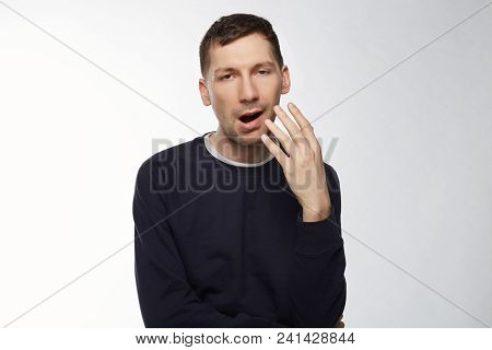 Young Caucasian Attractive Man Tired And Sleepy, Yawning, Try To Cover Mouth With Hand After Sleeple