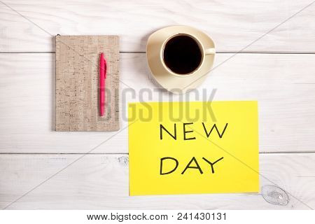Coffee Cup,note Book And Text New Day On Wooden Table.