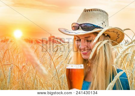 Young Sexy Woman In Cowboy Hat Stands In Barley Field And Holds A Glass Of Beer During Sunset