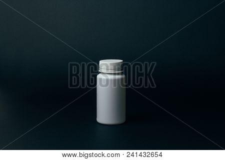 One White Pill Bottle On Black Background. Storage Pills. Vitamins. Release Pills.