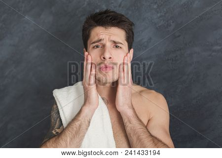 To Shave Or Not To Shave. Handsome Pensive Tattooed Man Touching His Face While Standing With Towel