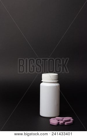 One White Pill Bottle On Black Background. Storage Pills. Vitamins. Release Pills. And Purple Pills,