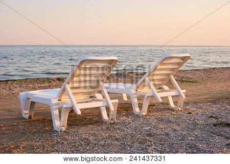 Close Up Two Half-turn Chaise Longues On The Sand. Concept Of Tranqil Evening On The Sea Beach With