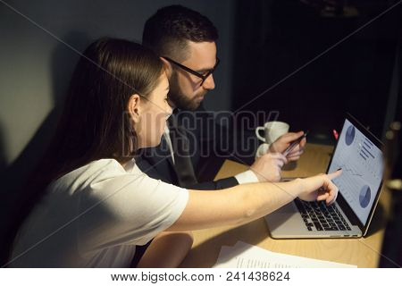 Concerned Colleagues Looking At Laptop, Analyzing Company Profits, Discussing Charts And Diagrams, N