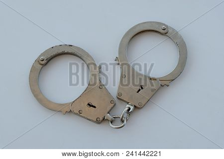 Top View Of A Steel Police Handcuffs On A White Background. The Theme Of Crime And Law.