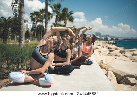 Full Length Portrait Of Calm Ladies Making Physical Exercises On Sea Coast. Tranquility During Train
