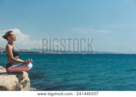 Side View Calm Female Meditating Near Endless Sea. Copy Space. Serene Lady Feeling Tranquility Conce