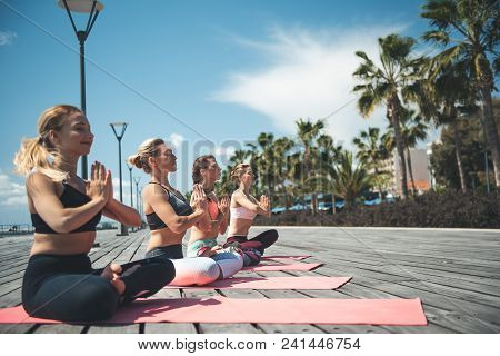 Side View Calm Females Meditating On Rugs At Seafront. Demure Friends During Workout Concept