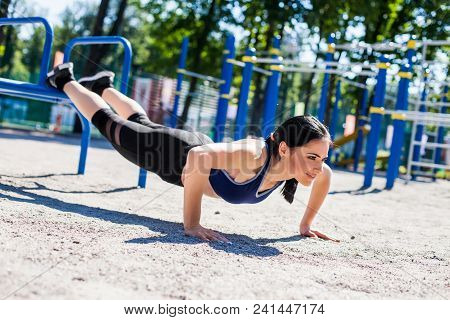 Young Sportive Woman Trainer In A Bright Blue Sport Bra And Black Leggings Doing Push Ups On The Spo
