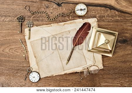 Antique Office Supplies And Accessories On Wooden Background. Vintage Used Paper With Feather Pen