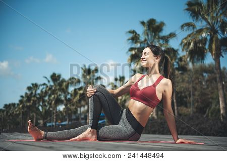 Full Length Portrait Of Cheerful Woman Practicing Yoga While Locating On Mat Outdoor. Glad Lady Doin