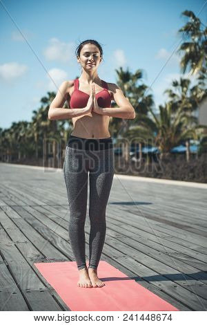 Full Length Portrait Of Smiling Female Expressing Calmness While Doing Yoga On Rug Outdoor. Happy Gi
