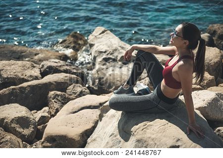 Full Length Side View Positive Girl Relaxing After Physical Exercise. She Looking At Endless Blue Wa