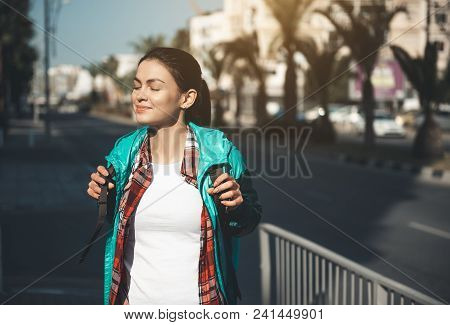Portrait Of Cheerful Young Female Walking At Street And Smiling. Happy Tourist Concept