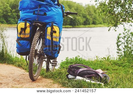 Bicycle with luggage stopped near the precipitous shore of the river. poster