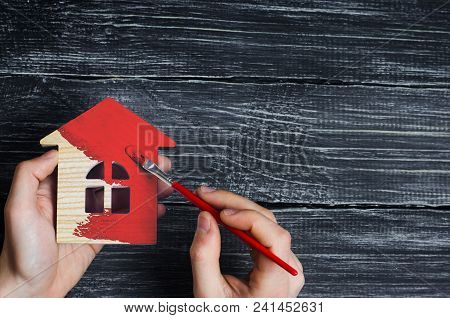 Hand Paints A House In To Red Color. Concept Of Repair, Hobby, Work. Repair And Painting Of Wooden H