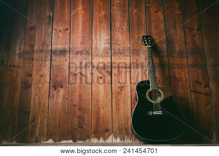 Acoustic Guitar On A Wooden Texture With Copy Space For A Text. Music And Leisure Concept. Guitar Ag