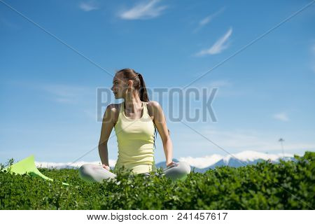 Peaceful Young Woman Meditating In Nature, On Green Grass, Practicing Yoga