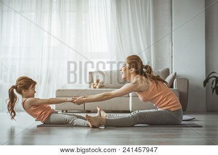 Who is stronger. Full length portrait of little girl trying to outweigh her mom during sport exercise on the floor. Both looking very happy and smile poster
