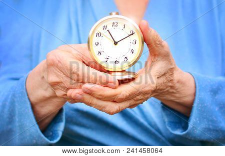 Old Age And Life Concept. Elderly Woman Holds A Clock In Wrinkled Hands, As A Reminder That Time Is