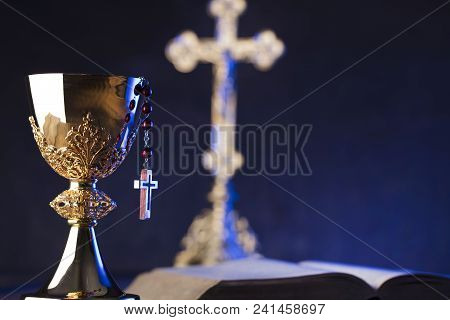 Roman Catholic Church Theme. The Cross, Holy Bible, Rosary And Golden Chalice On Violet Background.