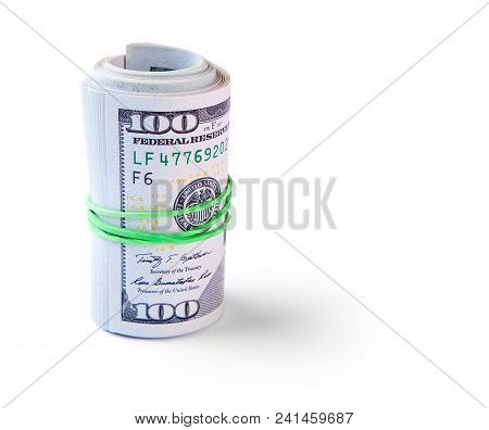 100 Dollar Bills Twisted Into Tube And Tied With An Elastic Band. Isolated On White Background.