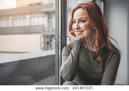 Portrait Of Red-haired Happy Woman Resting At Home. She Is Smiling While Looking Through Window With