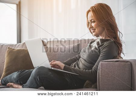 Attractive Red-haired Lady Sitting On Couch In Her Cosy Room And Typing On Her Computer. She Is Happ