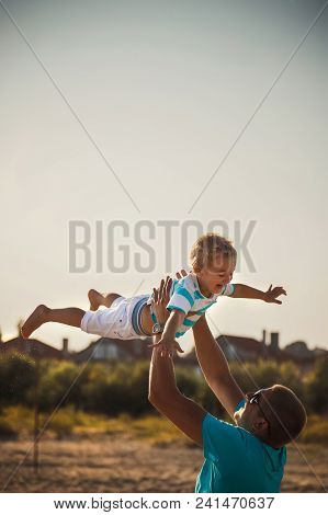 Happy Father And Son Playing Together At Beach. Father Throwing His Son In The Air.
