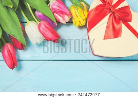 Colorful Spring Tulip Flowers With Decorative Giftbox On Light Blue Wooden Background As Greeting Ca